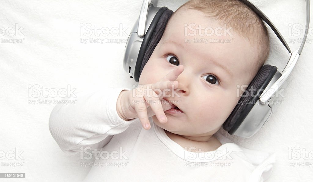 baby boy with headphone lies on back stock photo