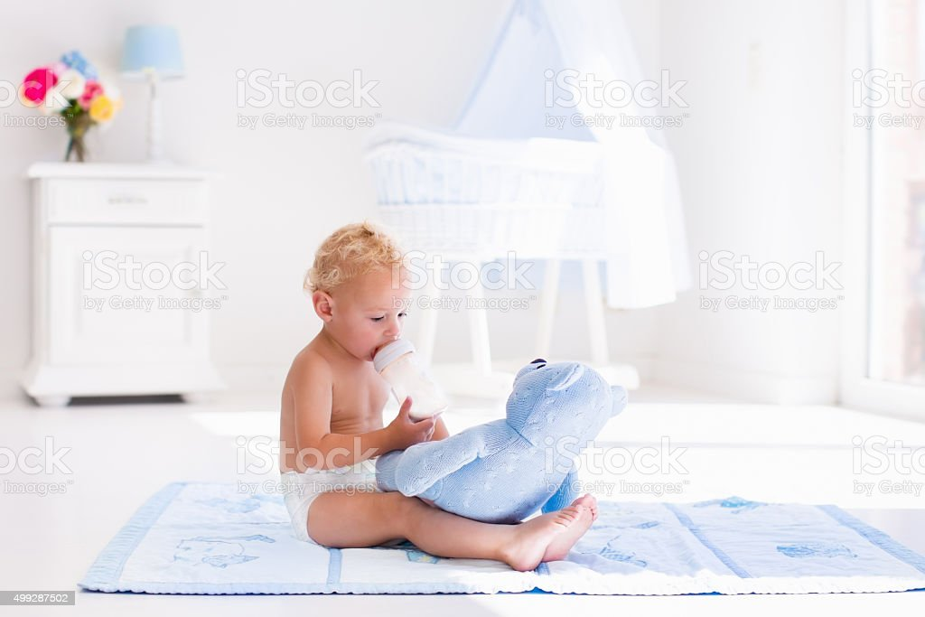 Baby boy with milk bottle in sunny nursery stock photo