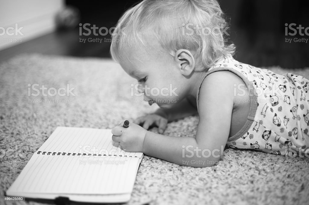 Baby boy writing in a notebook stock photo