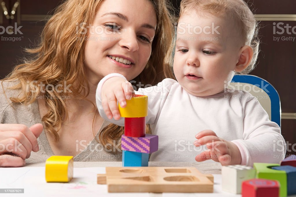Baby building a tower of wooden blocks with mother stock photo