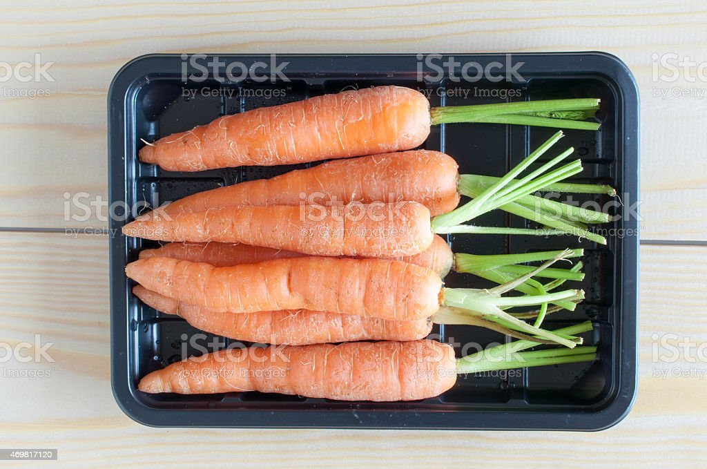 Baby carrots in a black container stock photo
