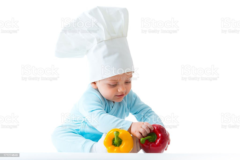 Baby chef with red and yellow peppers stock photo