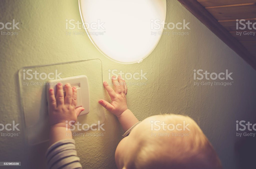 Baby child switching on / off the light stock photo
