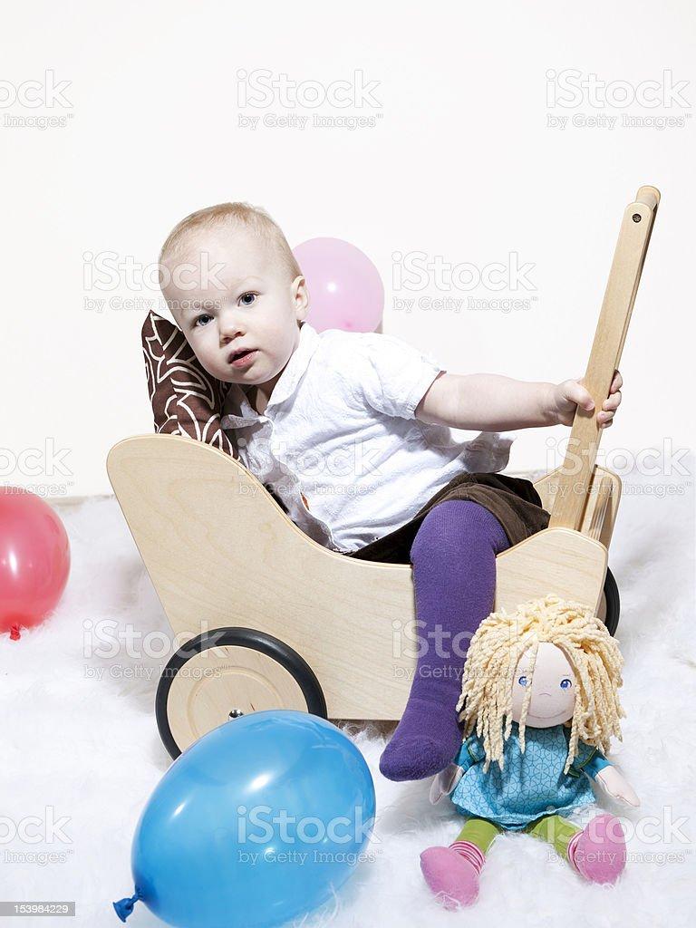 Baby climbing into dolls pram royalty-free stock photo