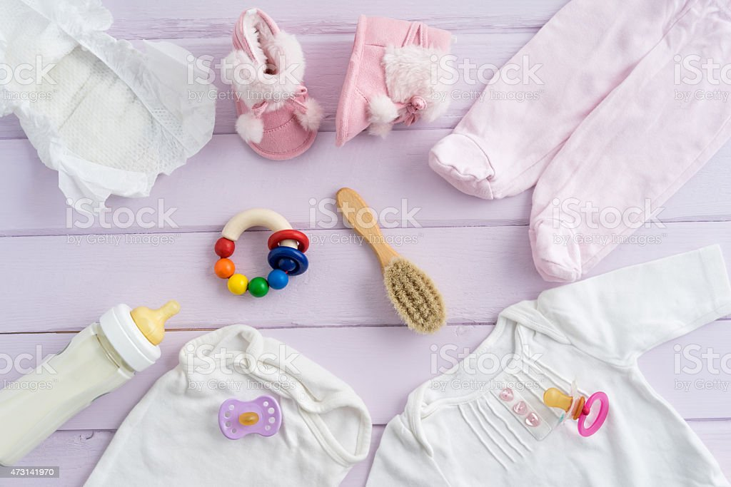 Baby clothes and accessories on light pink wooden surface stock photo