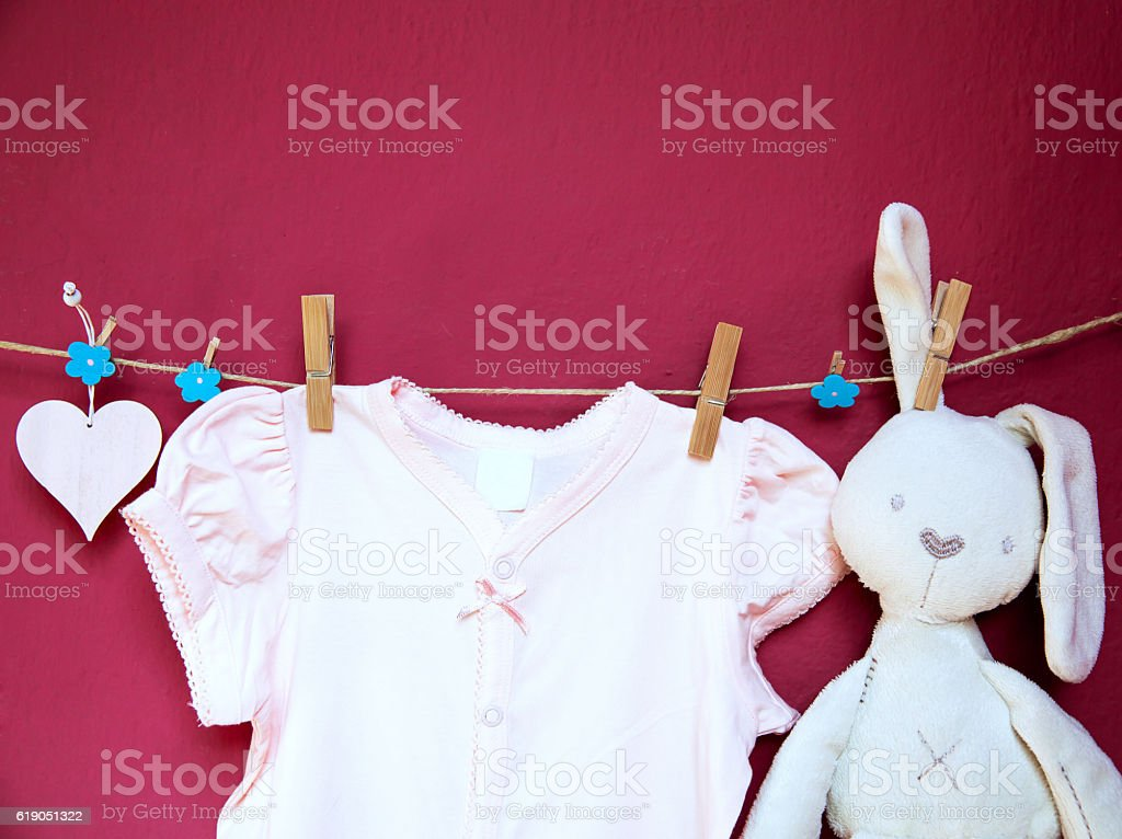 Baby clothes and goods hanging on the clothesline. stock photo
