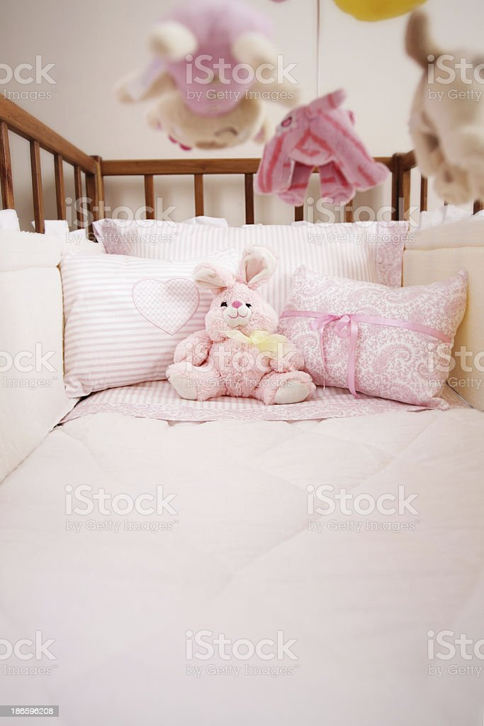 Baby crib with pink cushions and soft animals hanging stock photo