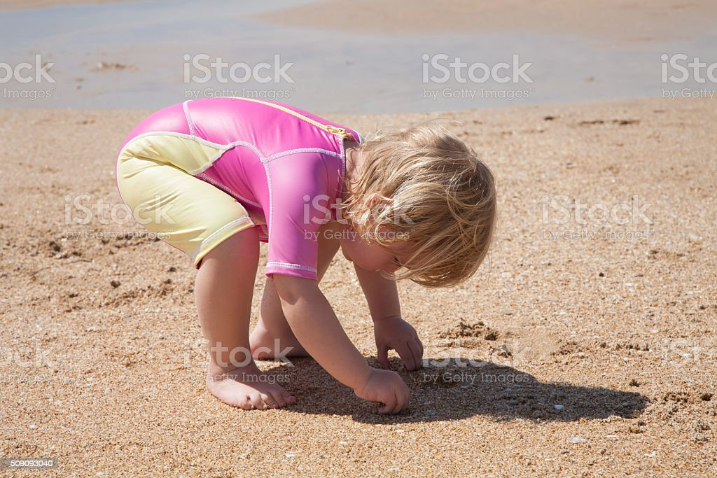 baby crouching at sand beach stock photo