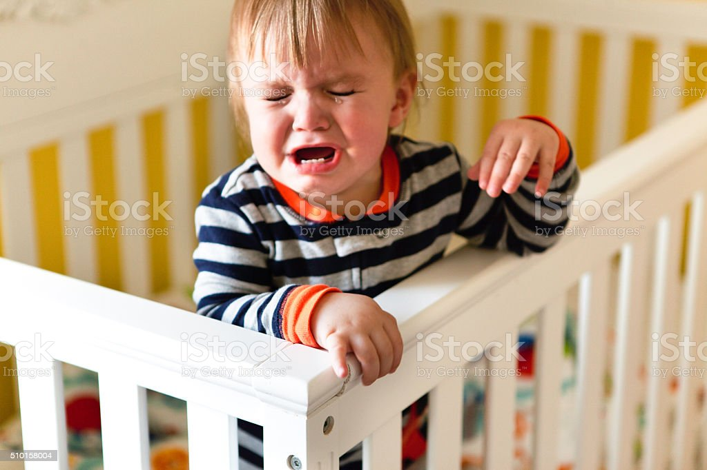 Baby Crying in Crib stock photo