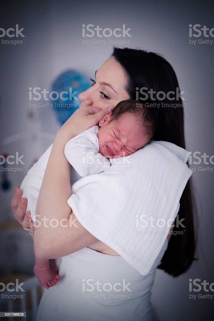 Baby crying on mothers shoulder stock photo