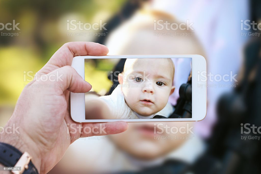 Baby cute in stroller with smart phone photo shot stock photo
