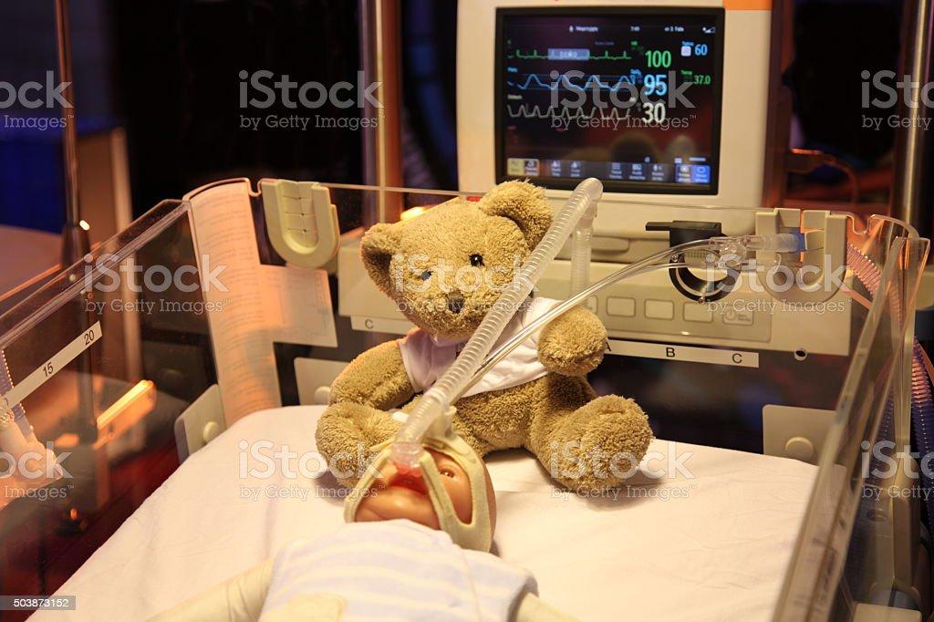 Baby doll in incubator. New born. Respirator machine. Teddy bear.