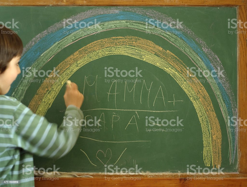 Baby Drawing a Rainbow at the Blackboard stock photo