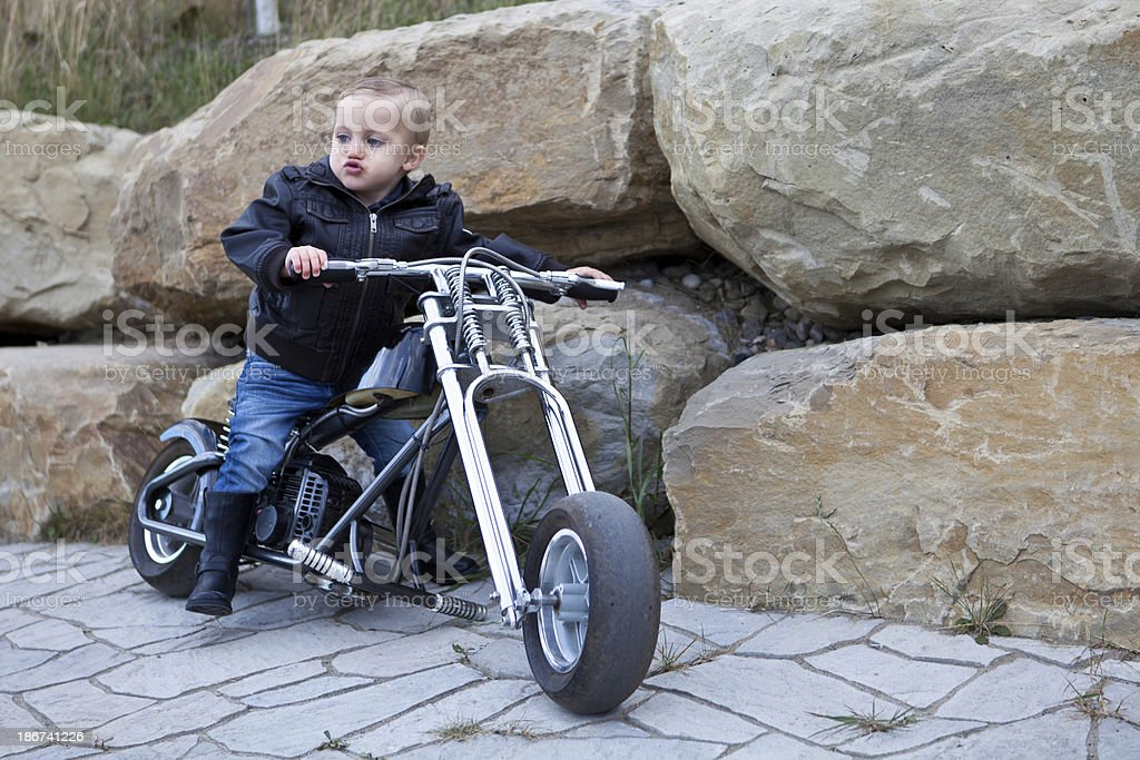 A baby dressed as a biker on a small motorbike stock photo