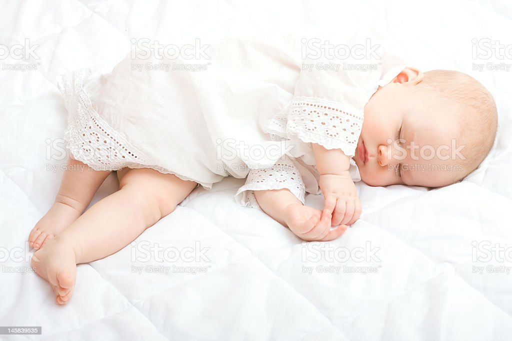 Baby dressed in a white gown sleeping on white sheets royalty-free stock photo