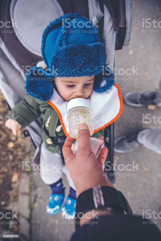 Baby drinking water from a baby bottle stock photo