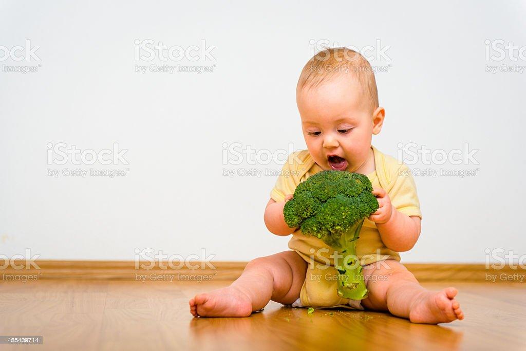 Baby eating broccoli stock photo