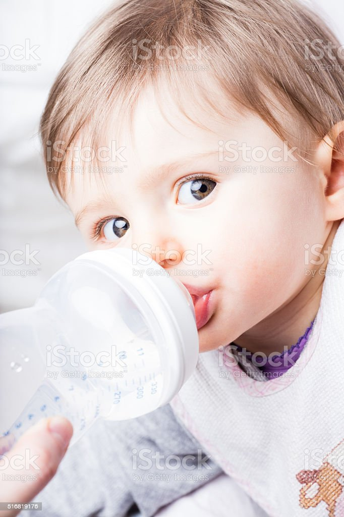 baby eating from her baby bottle stock photo