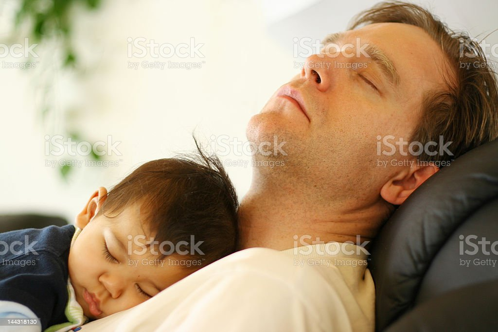Baby fast asleep on Daddy's chest royalty-free stock photo
