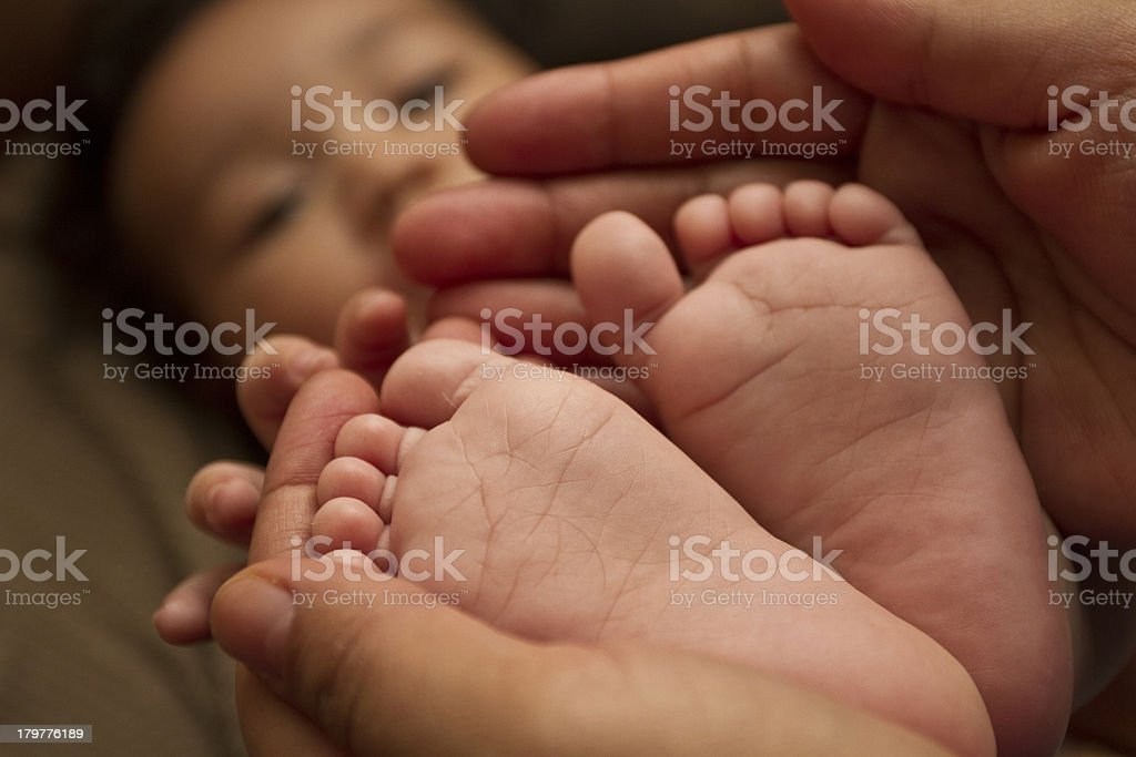 Baby feet closeup with mom holding him royalty-free stock photo