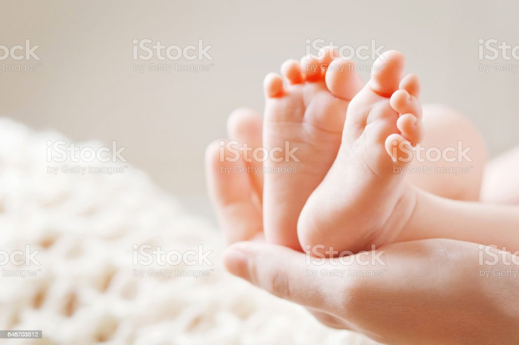 Baby feet in mother hands. Mom and her Child. stock photo