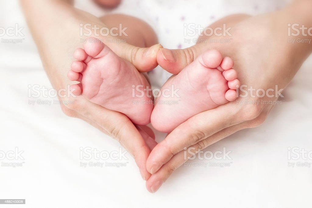 Baby feet in mother hands stock photo