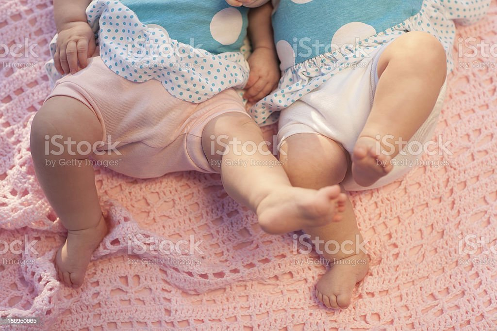 Baby feet in motion. Twins lying on a pink blanket. royalty-free stock photo