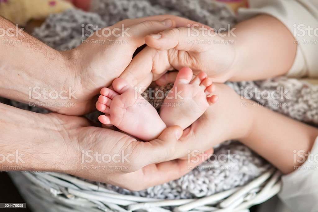 Baby feet in parents hands. Happy Family concept. stock photo