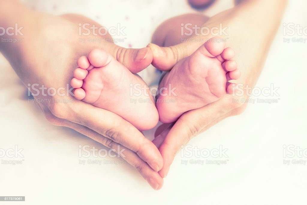 Baby feet in the mother hands stock photo