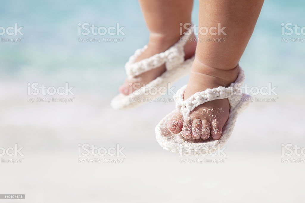 baby feet in white sandals at the Caribbean beach royalty-free stock photo