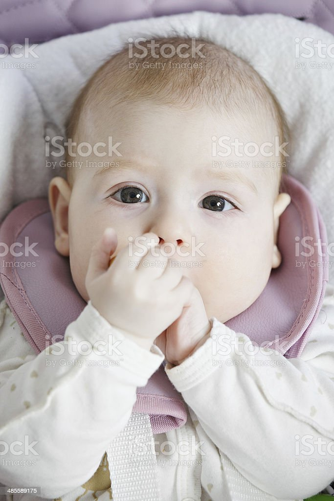 Baby folding hands at mouth stock photo