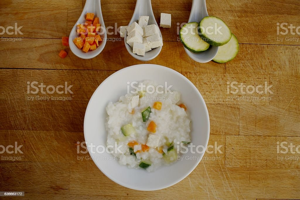 Baby food boiled rice with courgette,tofu and carrot stock photo