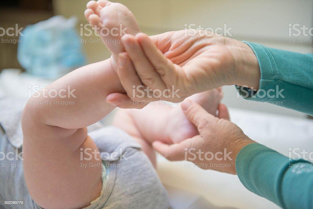 baby foot in mother's hands stock photo