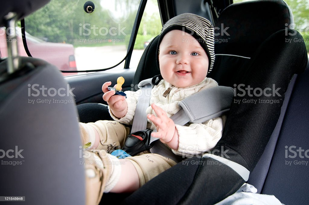 A baby front facing early in car seat and unsafely strapped stock photo