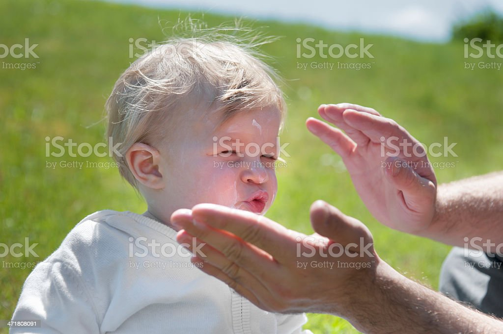 baby getting sun cream on her face royalty-free stock photo