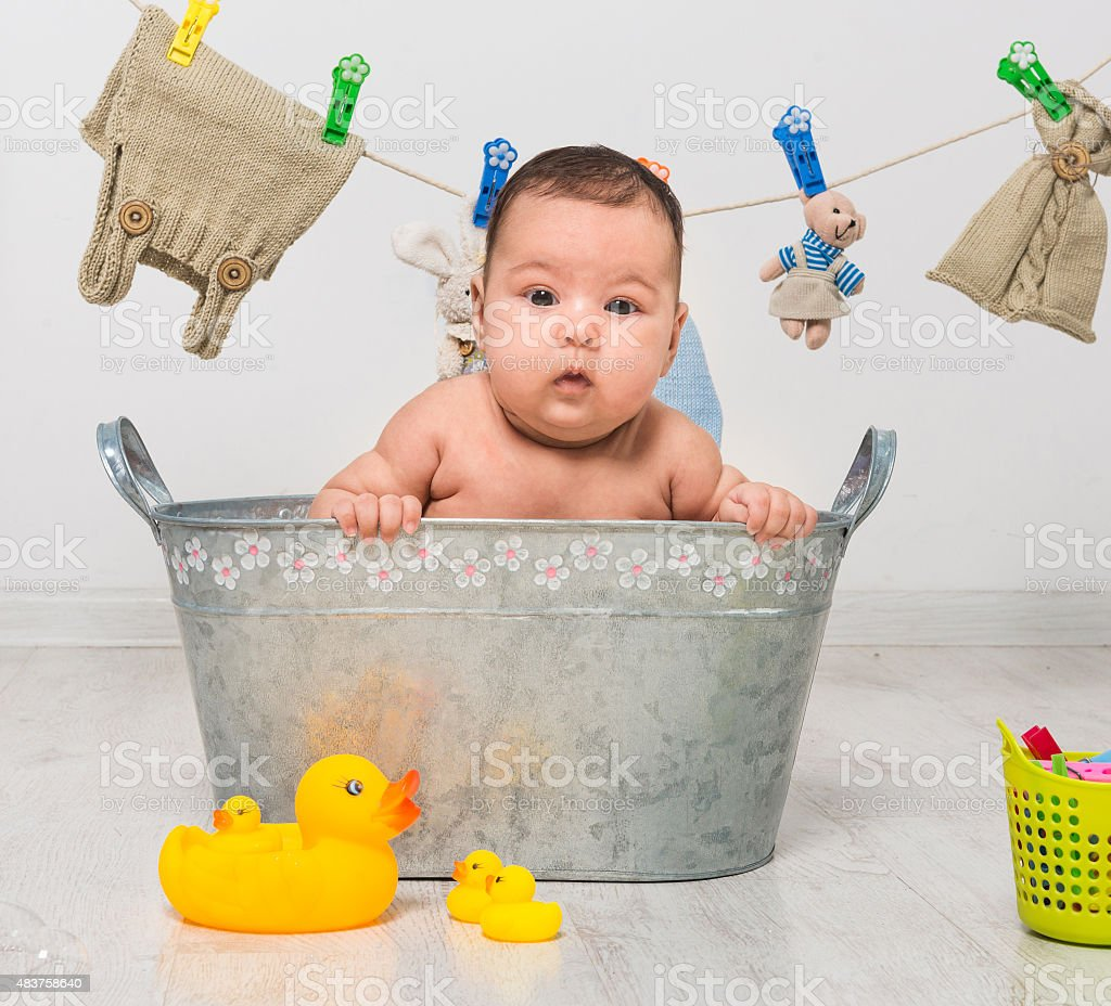 baby girl bathes in a  trough stock photo