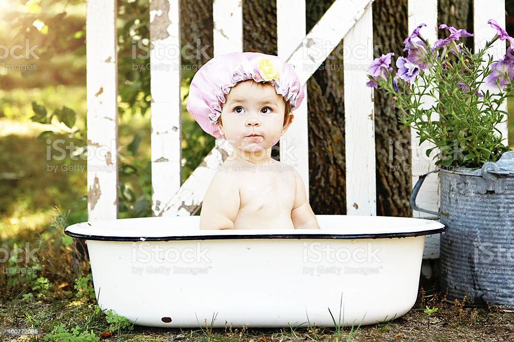 Baby Girl Bathing in Antique Tub Outside royalty-free stock photo