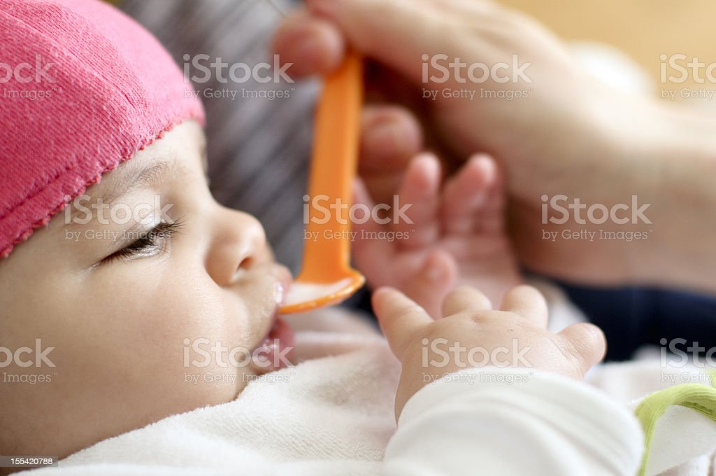 Baby girl being spoon fed with orange spoon stock photo