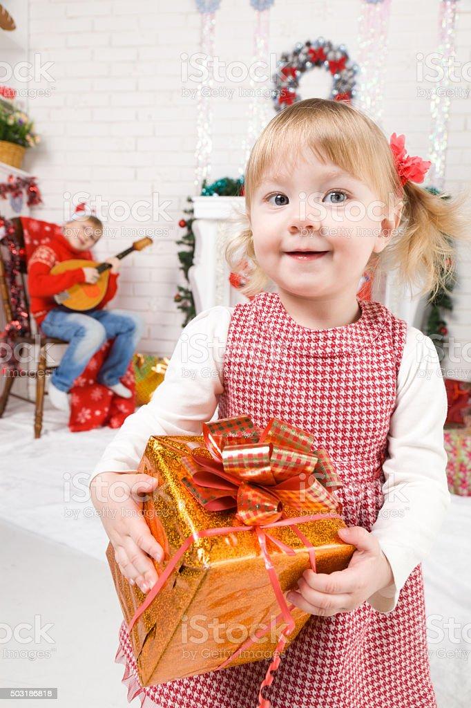Baby girl beside Christmas tree stock photo