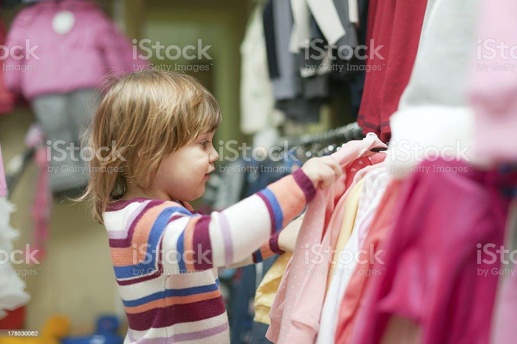 baby girl  chooses clothes at shop royalty-free stock photo