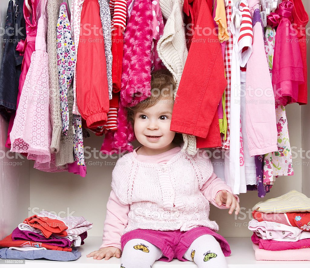 Baby girl choosing her clothes stock photo