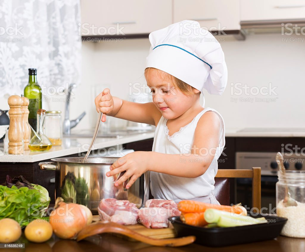 Baby girl cooking with meat stock photo