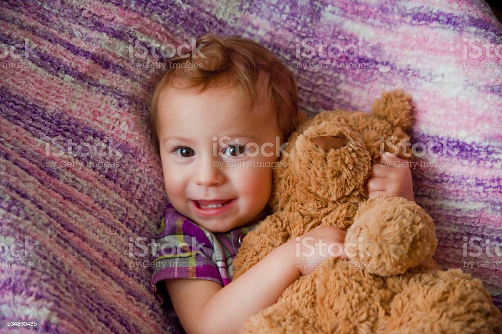 Baby Girl Cuddling With Teddy Bear stock photo