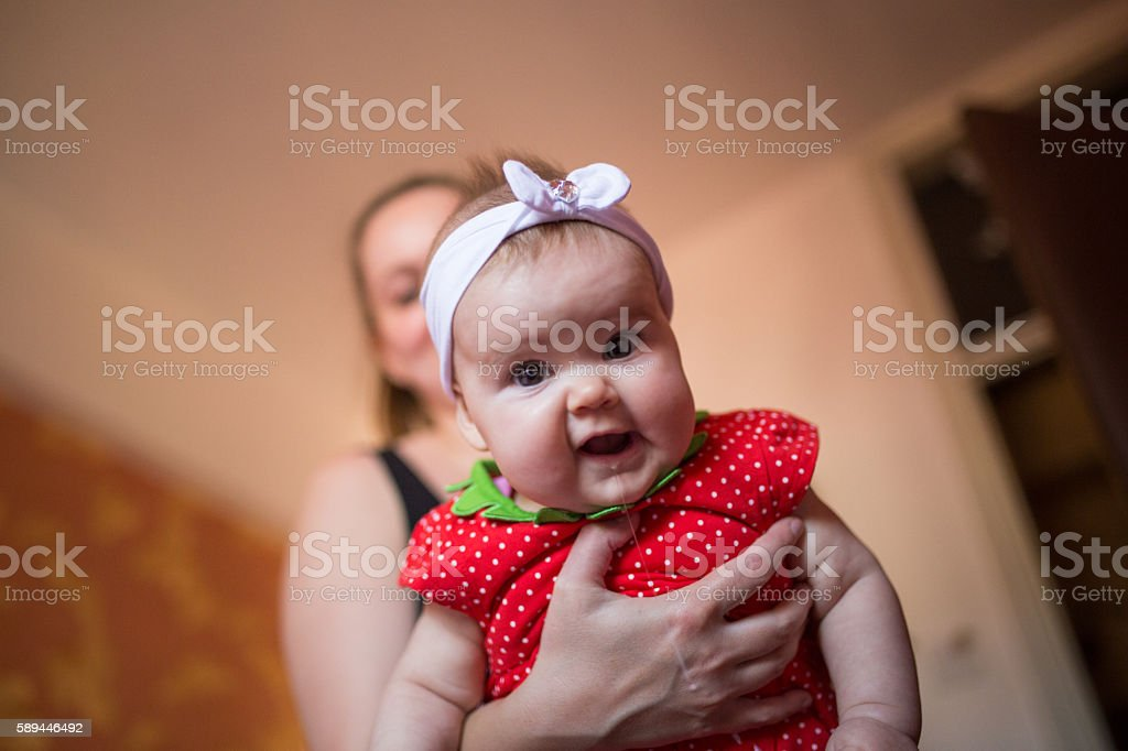 Baby girl drooling in mother's arms stock photo
