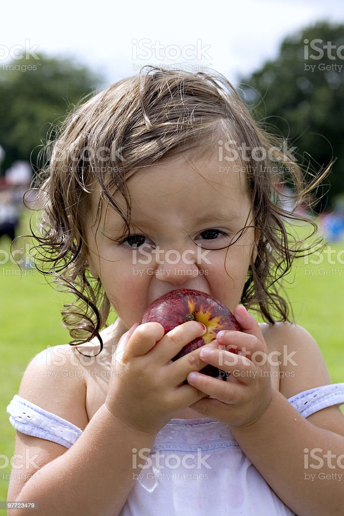 Baby girl eating an apple royalty-free stock photo