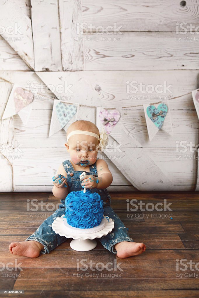 Baby Girl Eating Her First Birthday Cake stock photo