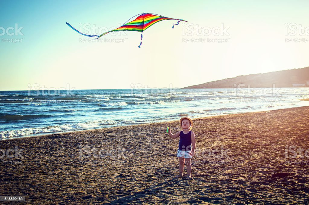 Baby girl flying kite together at tropical sunny beach stock photo