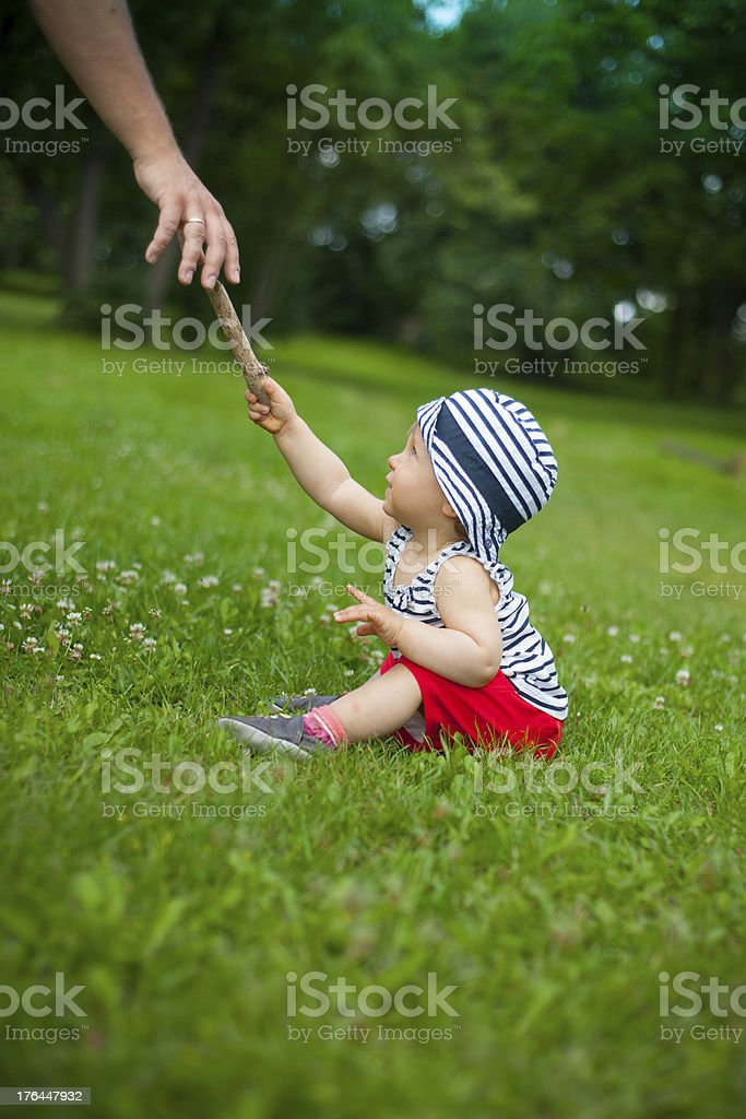 Baby girl giving a stick to her father royalty-free stock photo