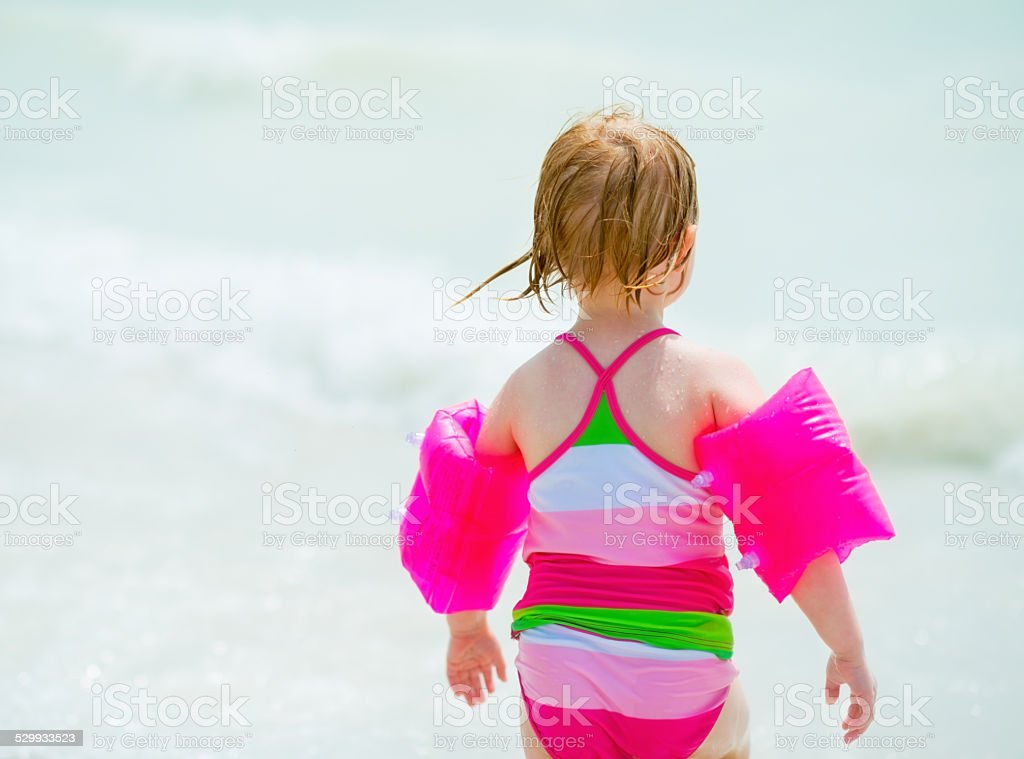 baby girl going into sea. rear view stock photo