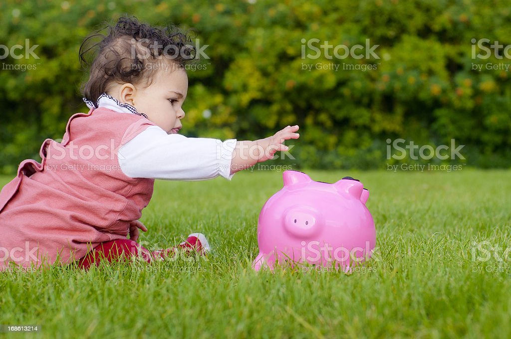 Baby Girl ( 8-9 Months old) Grabbing Piggy Bank, Outdoors royalty-free stock photo